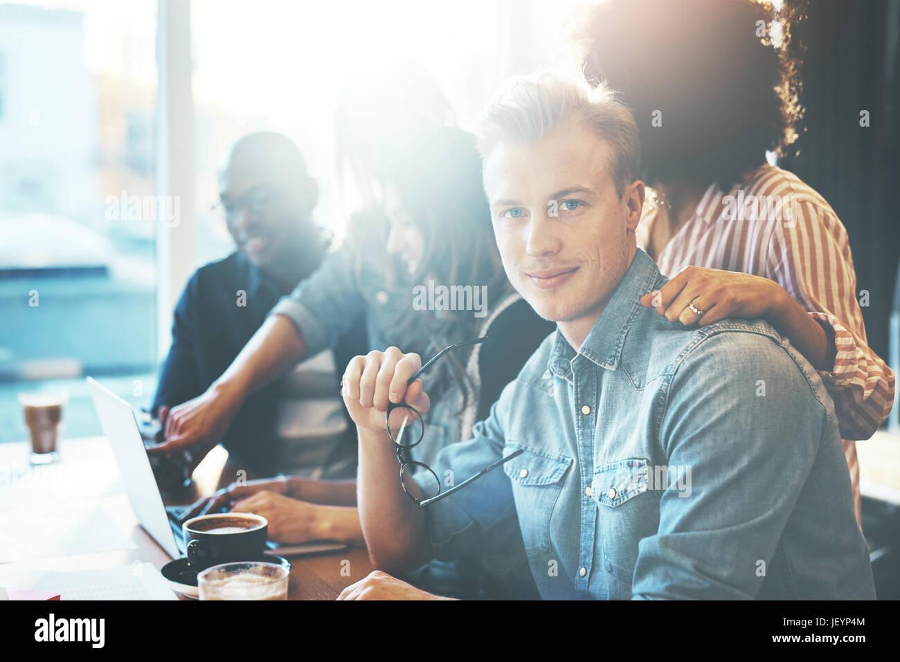 Gut aussehender Mann hält Brillen sitzen am Konferenztisch mit Kollegen. Helle Fenster im Hintergrund. Stockbild