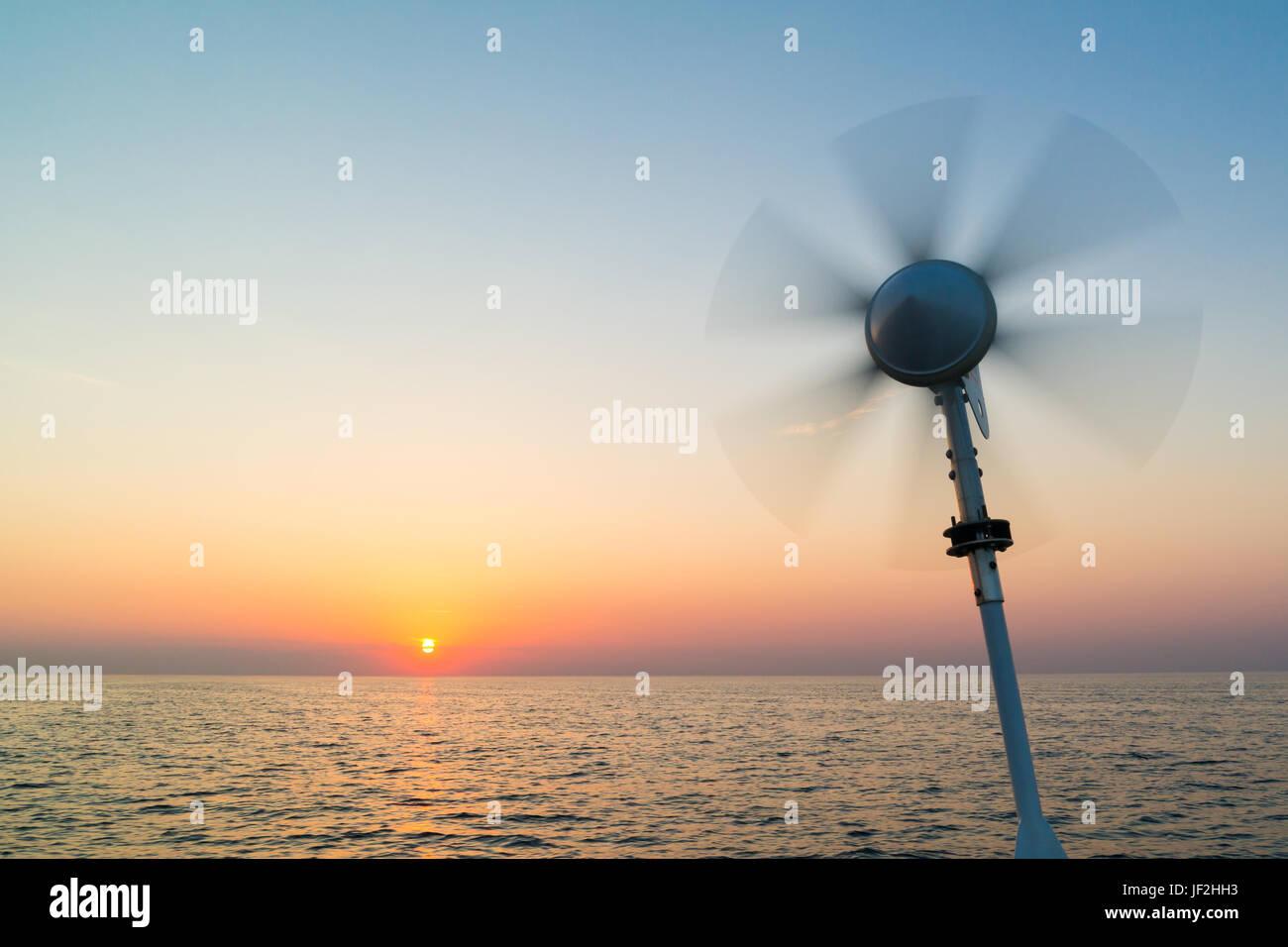 Marine Windturbine auf Segelboot mit dem Drehen der Lamellen durch Windkraft an Bord Akkus auf Nordsee bei Sonnenuntergang, Stockbild