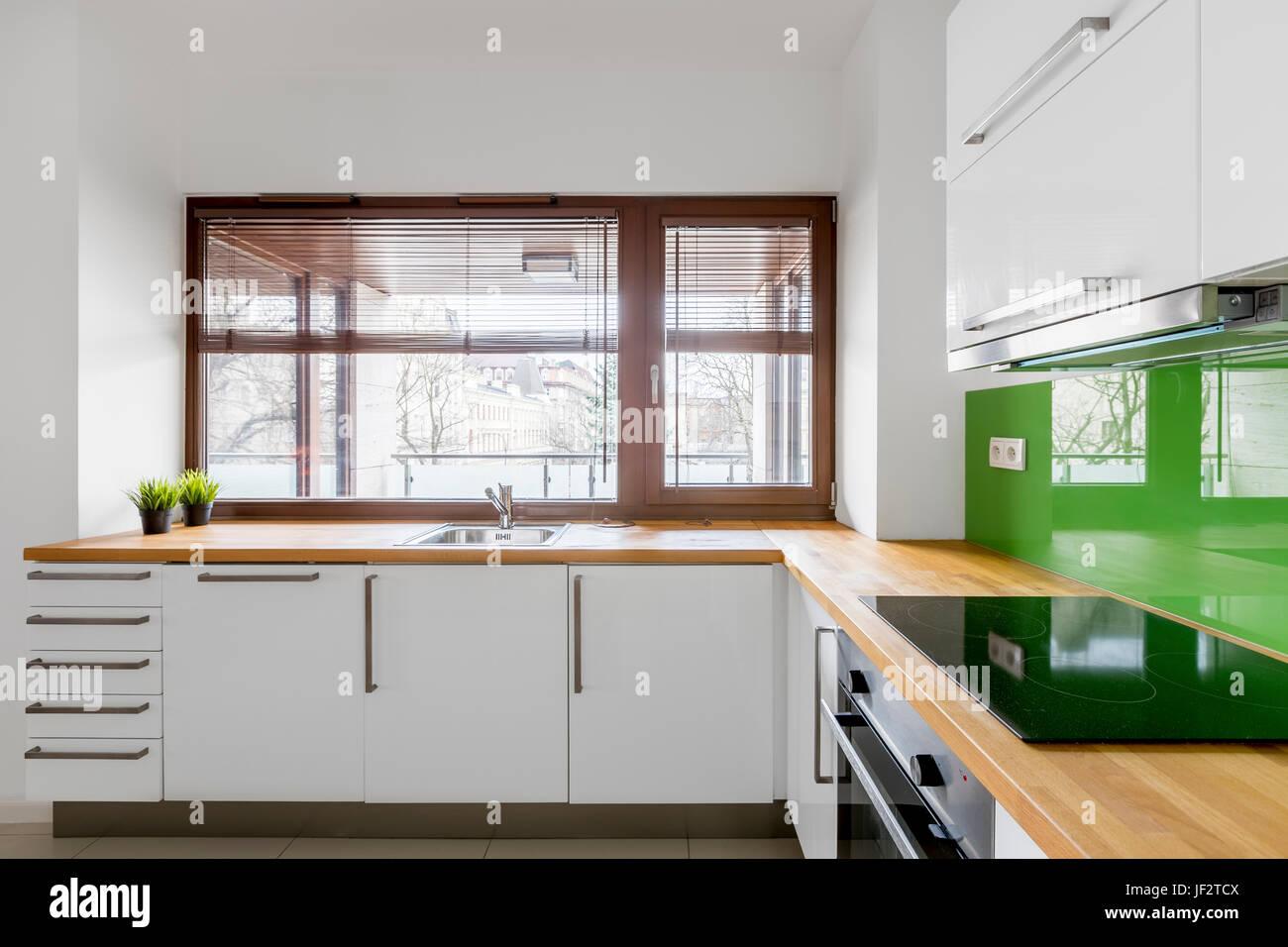 Weiße Küche Mit Modernen Schränke, Grüne Backsplash Und Fenster Stockbild