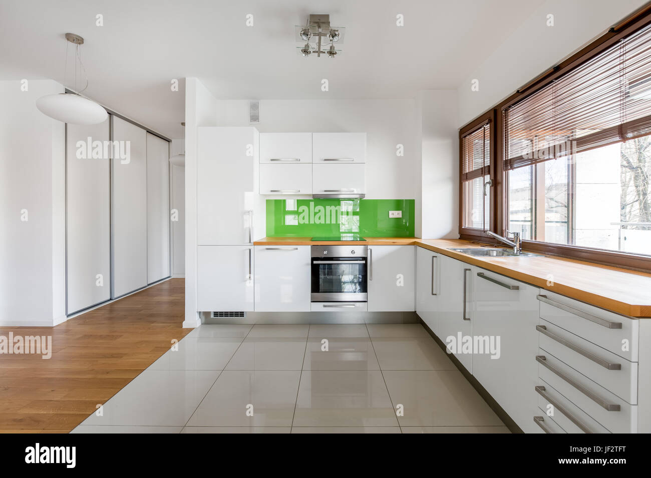 Weiße, Offene Küche Mit Fenster, Grüne Backsplash Und Hölzerne  Arbeitsplatte Stockbild
