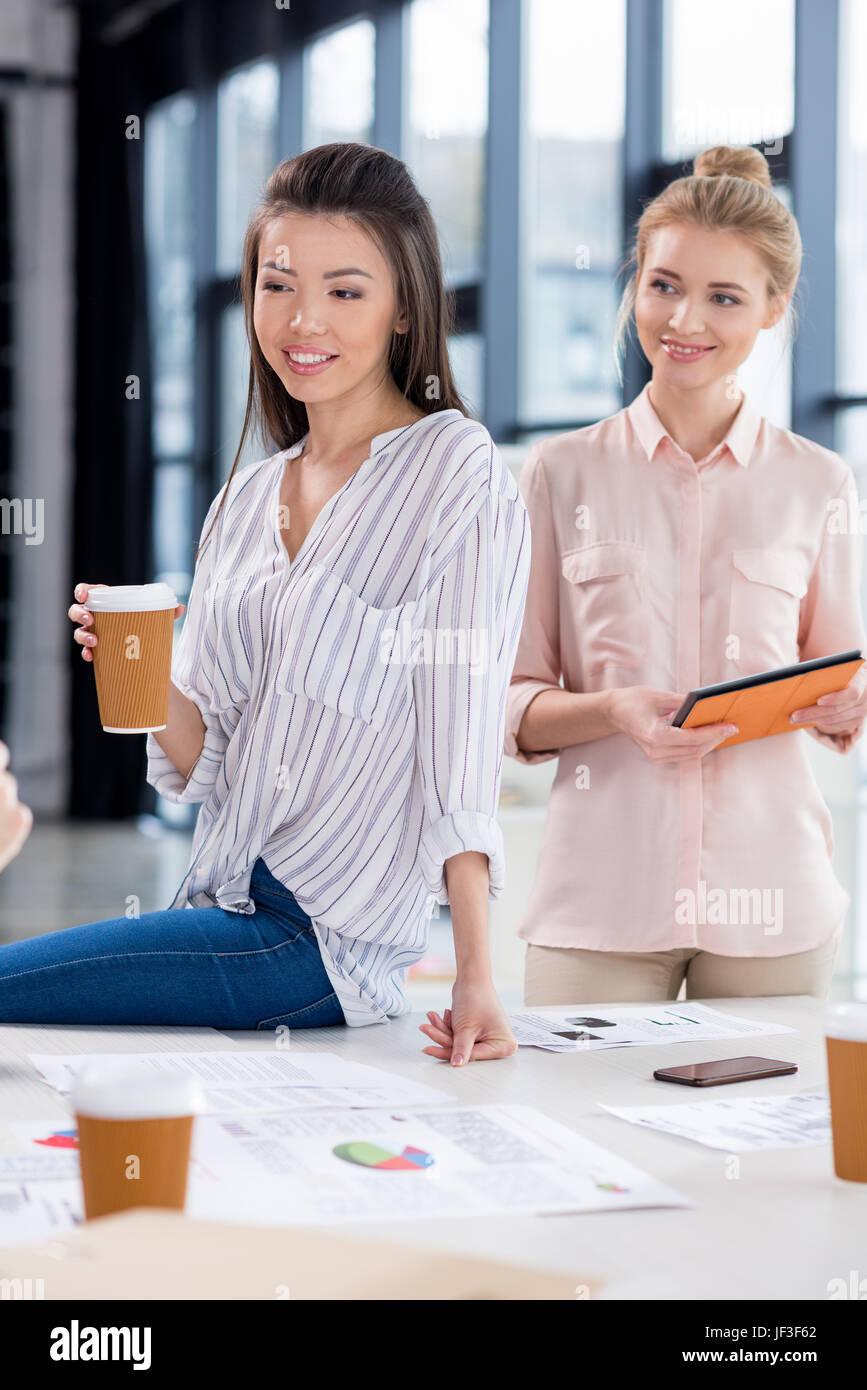 junge Unternehmerinnen mit Kaffee und Tablet am modernen Arbeitsplatz Stockbild