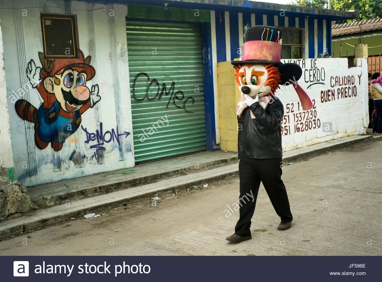 Ein Mann trägt einen Cartoon-Maske für den Tag der toten Feier geht es vorbei an einen Cartoon-Charakter Stockbild