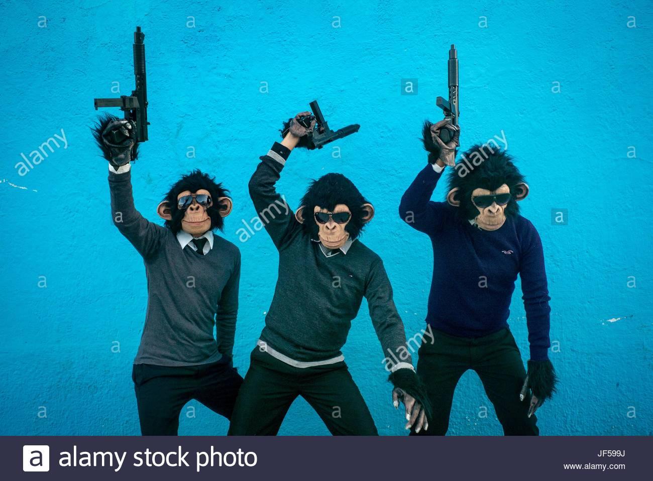 Teilnehmer tragen Affe Schimpanse Kostüme, schwingen Spielzeug Waffen während eines Tages der toten Feier. Stockbild