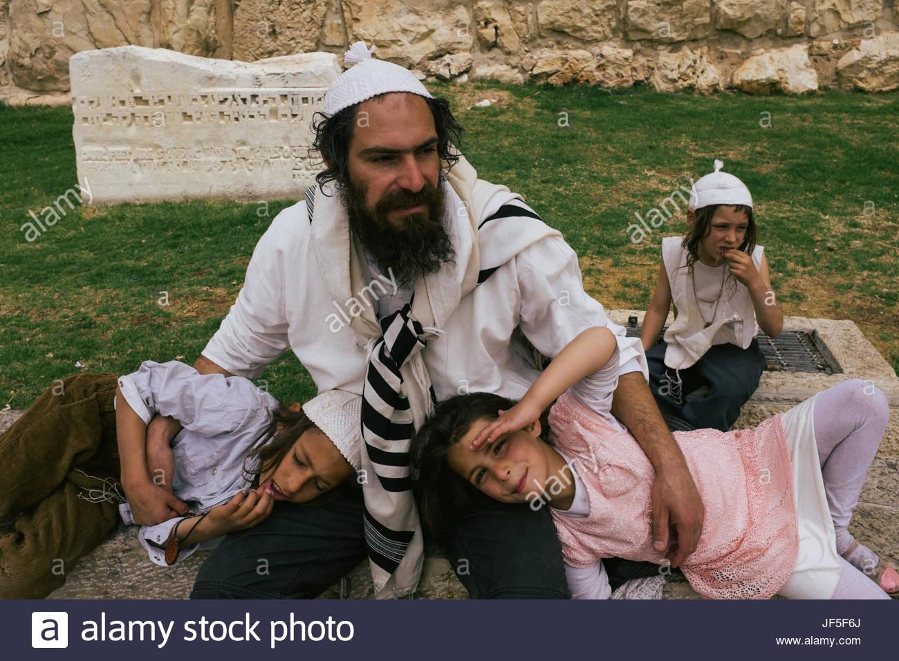 Ein jüdischer Mann liegt mit seinen Kindern in der Nähe der jüdischen Viertel der Altstadt von Jerusalem. Stockbild