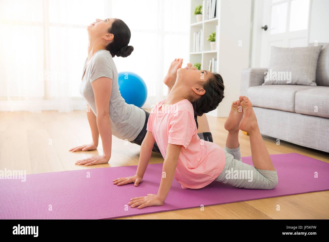 asiatische Mutter und Tochter Yoga Übungen im Urlaub in den Raum zu ...