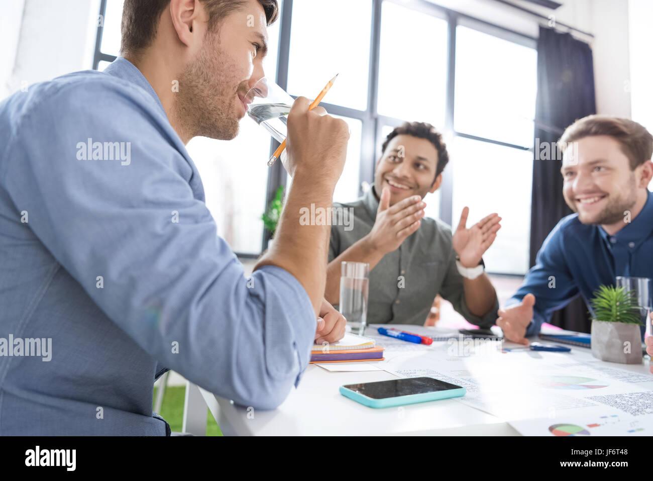 Lächelnde junge Geschäftsleute Trinkwasser und diskutieren neue Projekt, Teamarbeit Geschäftskonzept Stockbild