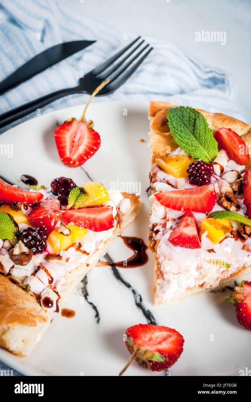 Sommer-Snacks. Essen für die Partei. Obst-Pizza mit Creme, Johannisbeeren, Joghurt, Erdbeeren, Mango, Pfirsiche, Stockbild