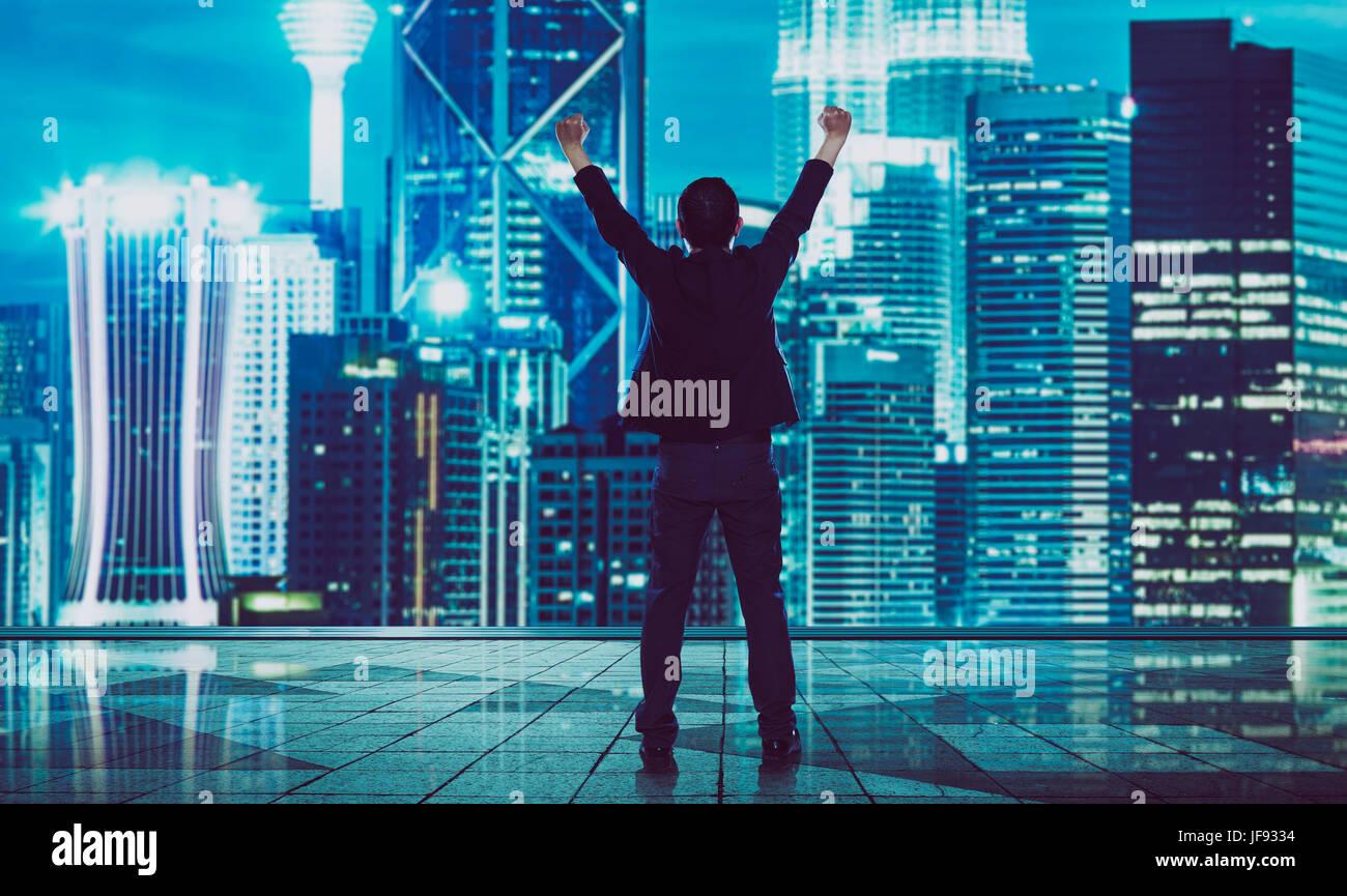 Rückansicht des aufgeregt Geschäftsmann mit Arme nach oben, verschwommene Morden Skyline der Stadt. Stockbild