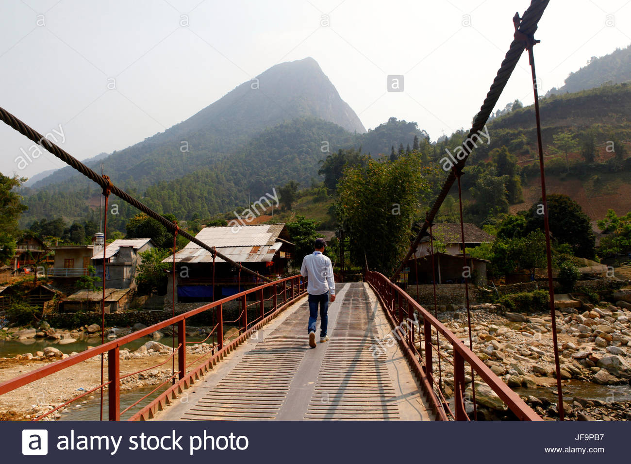 Ein Mann geht über eine Brücke in Sapa, Vietnam. Stockbild