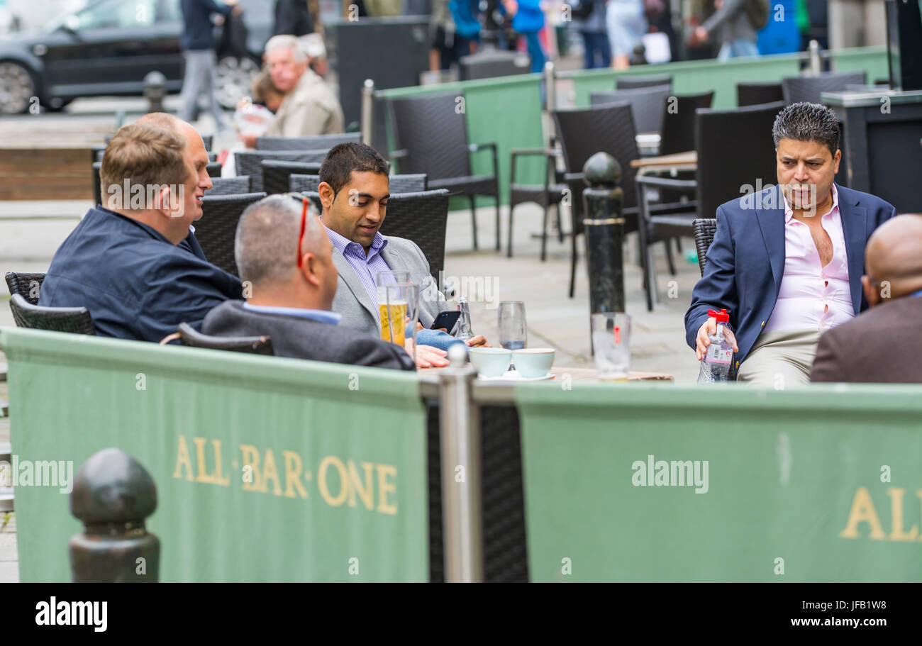 Smart mittlere gealterte Männer in Anzügen, die draußen sitzen in einer Bar in Brighton. Stockbild