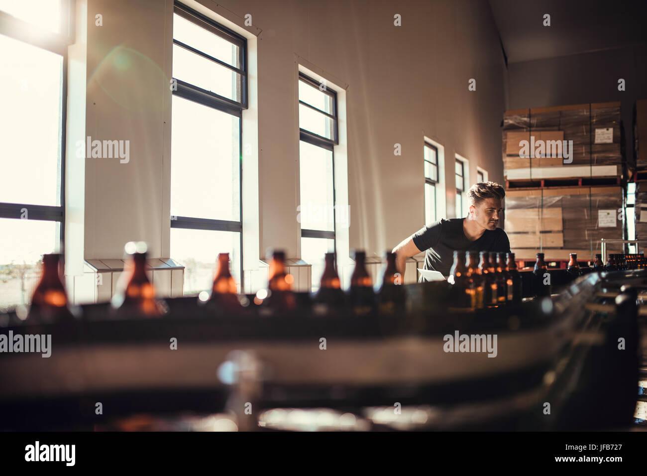 Junger Mann, die Überwachung der Produktion von Craft Bier in der Brauerei. Mann, der auf Alkohol verarbeitenden Stockbild