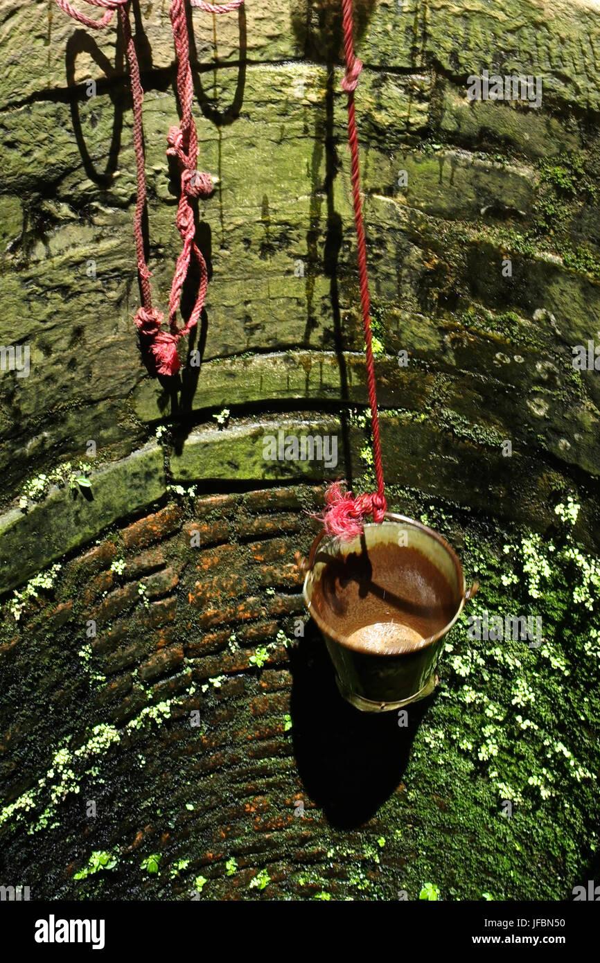 Ein Eimer hängt in einem öffentlichen Brunnen. Stockbild