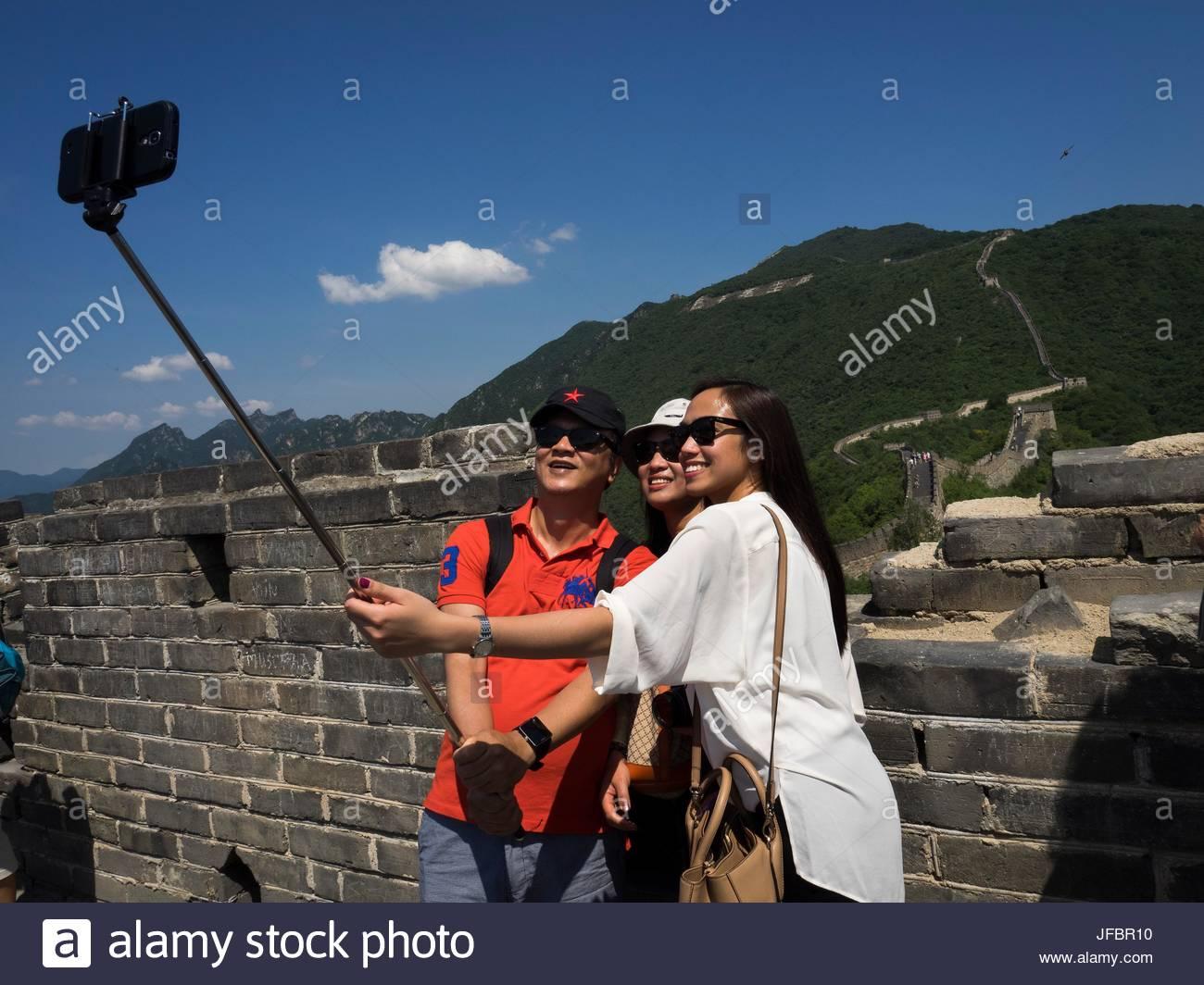 Jugendliche schießen ein Selbstporträt auf der chinesischen Mauer mit einem Handy. Stockbild