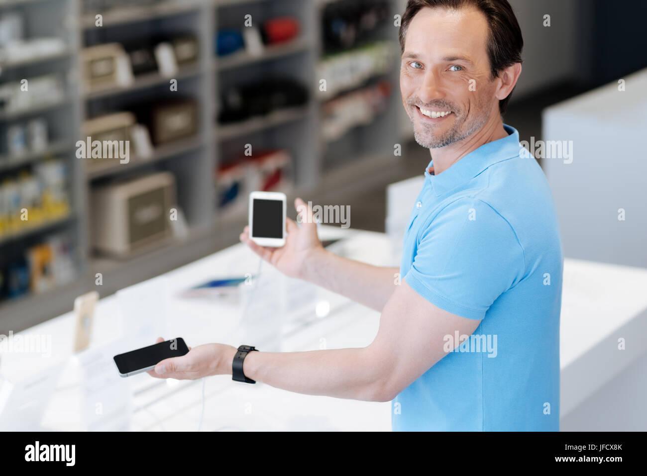 Wissen Sie nicht, welches man wählen. Strahlende Mann grinste breit beim Einkaufen für ein neues Handy Stockbild