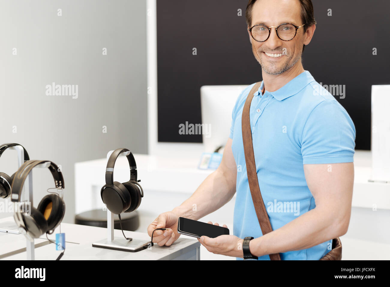 Was für ein perfektes Paar Kopfhörer. Positiven Mann grinsend weit während seiner Smartphone Schwarz Stockbild