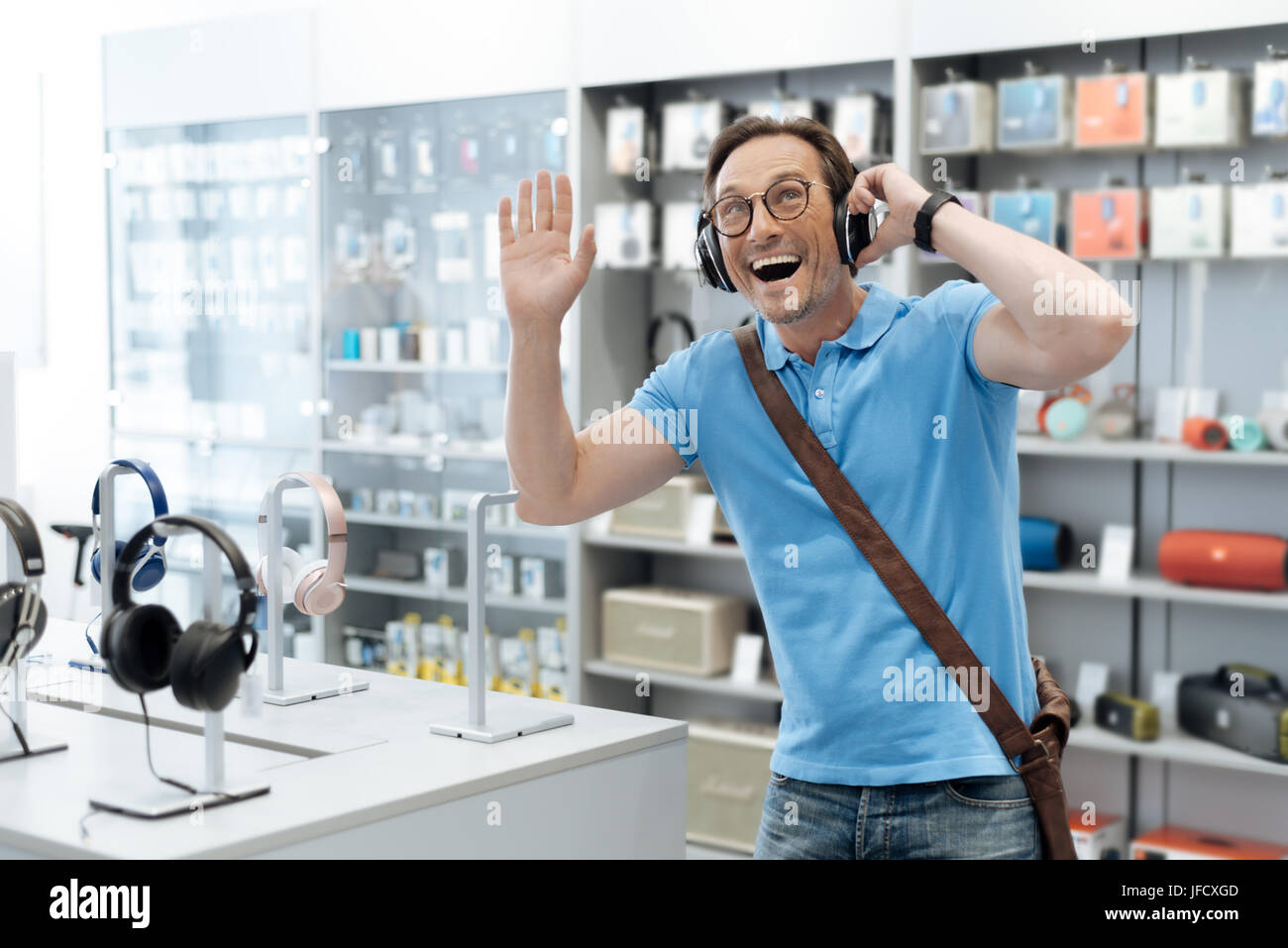 Das Lied von meiner Kindheit. Taille bis Schuss von einem extrem aufgeregt Mann testet das neueste Modell der Kopfhörer Stockbild