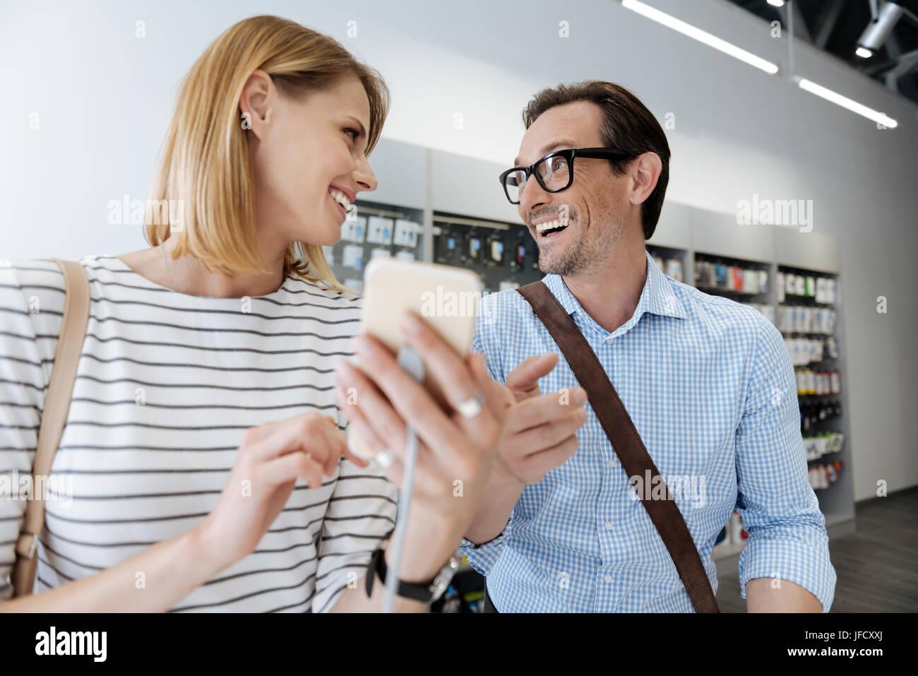 Sie müssen um es zu kaufen. Emotionalen Paar tragen legere Kleidung strahlend während und Überprüfung einer Vorlage Stockfoto