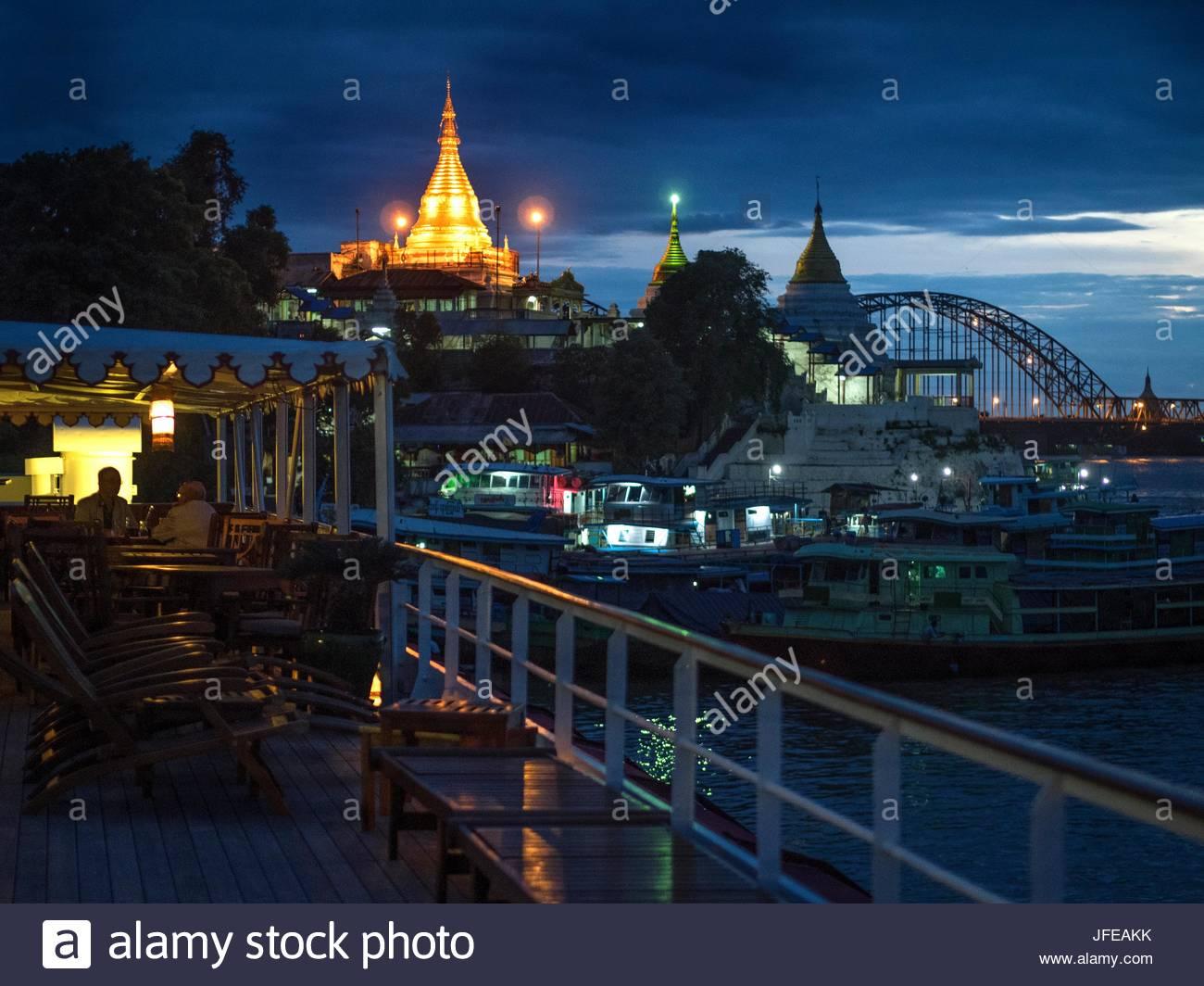 Pagode Shwe Kyet Kya leuchtet Gold im Hintergrund der Boote auf dem Irrawaddy-Fluss angedockt. Stockbild