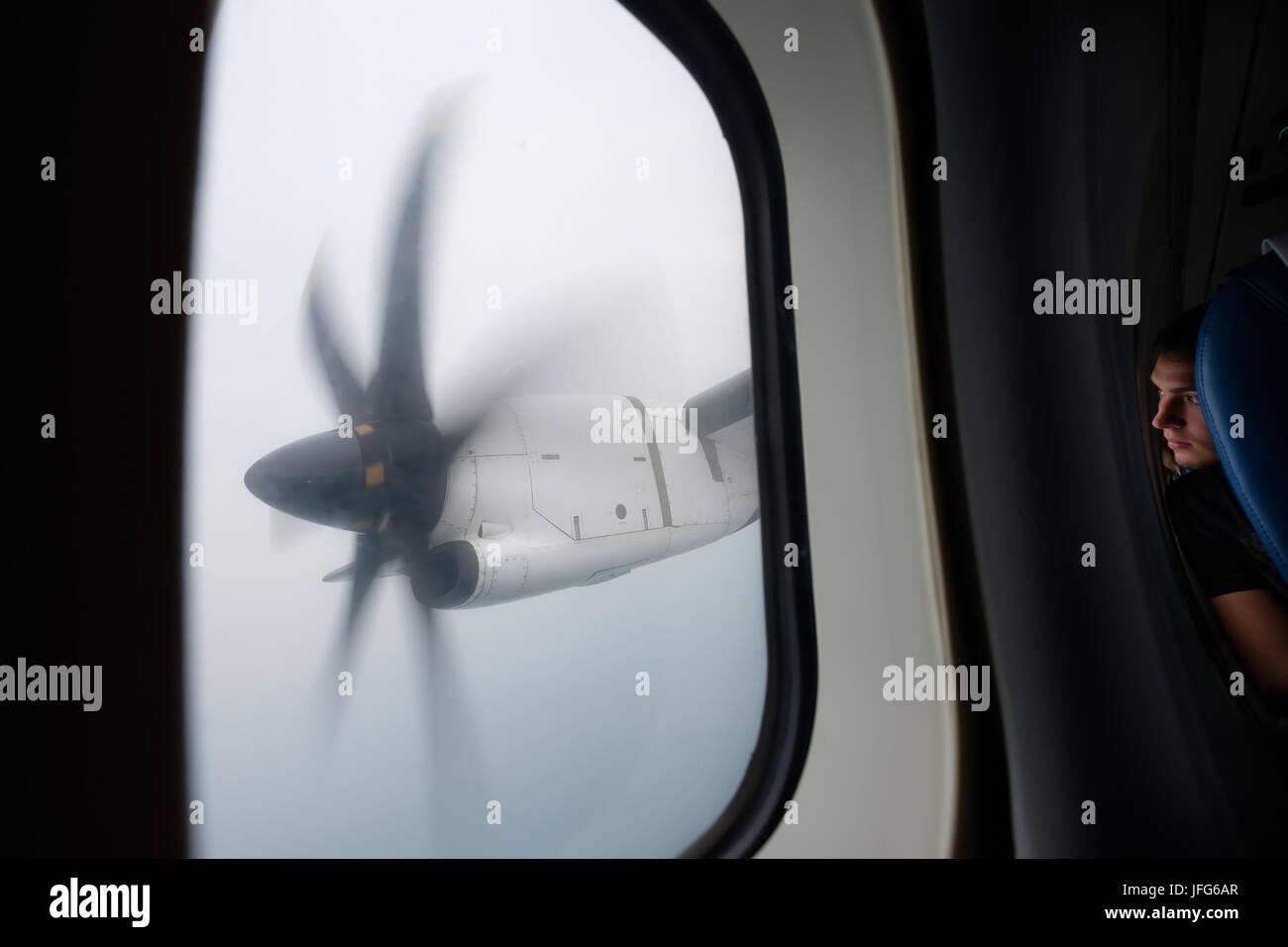 Person Blick aus dem Fenster eines Flugzeuges am Propeller Motor Stockbild