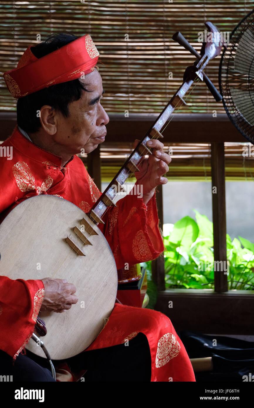 Alte Mann spielt ein Mond laute Zweisaitiges vietnamesischen traditionellen Musikinstrument Stockbild