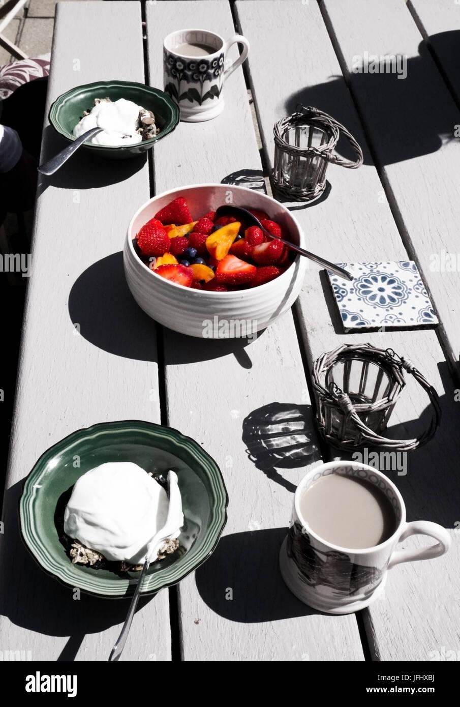 weißen hölzernen Tischplatte mit einem gesunden Frühstück auf sie in der Mitte eine bunte Obstschale Stockbild
