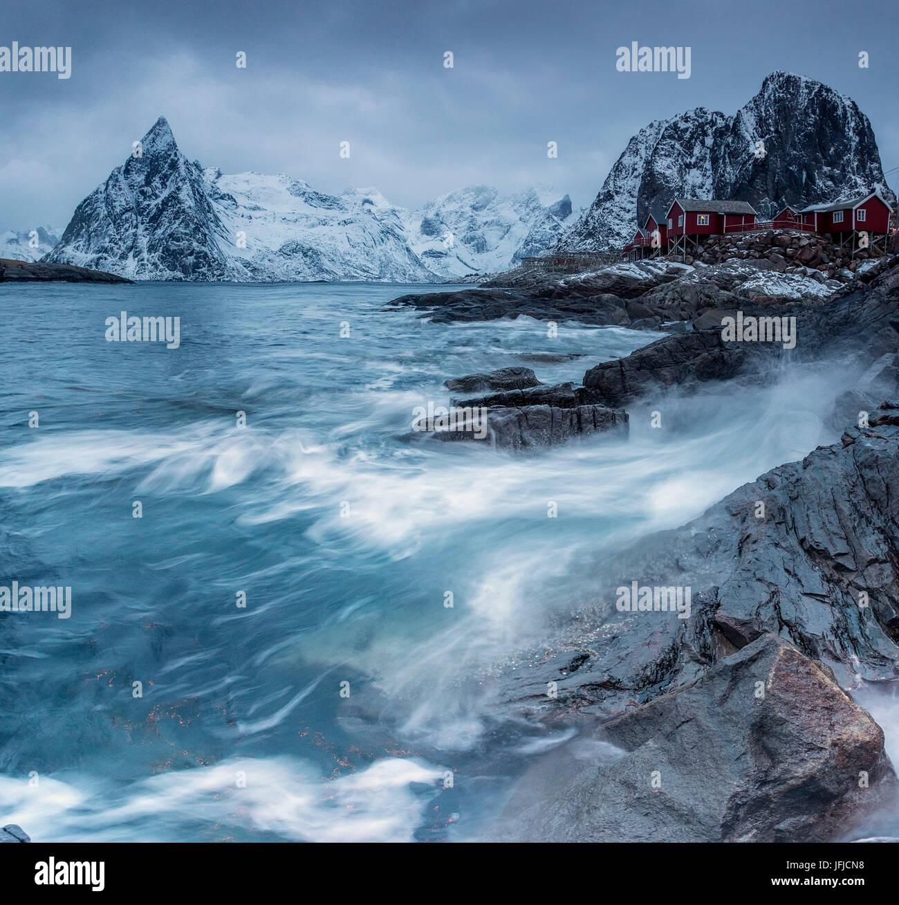 Wellen, die auf den Klippen in der Nähe von den Häusern der Fischer, Hamnøy, Lofoten Inseln Norwegen Stockbild