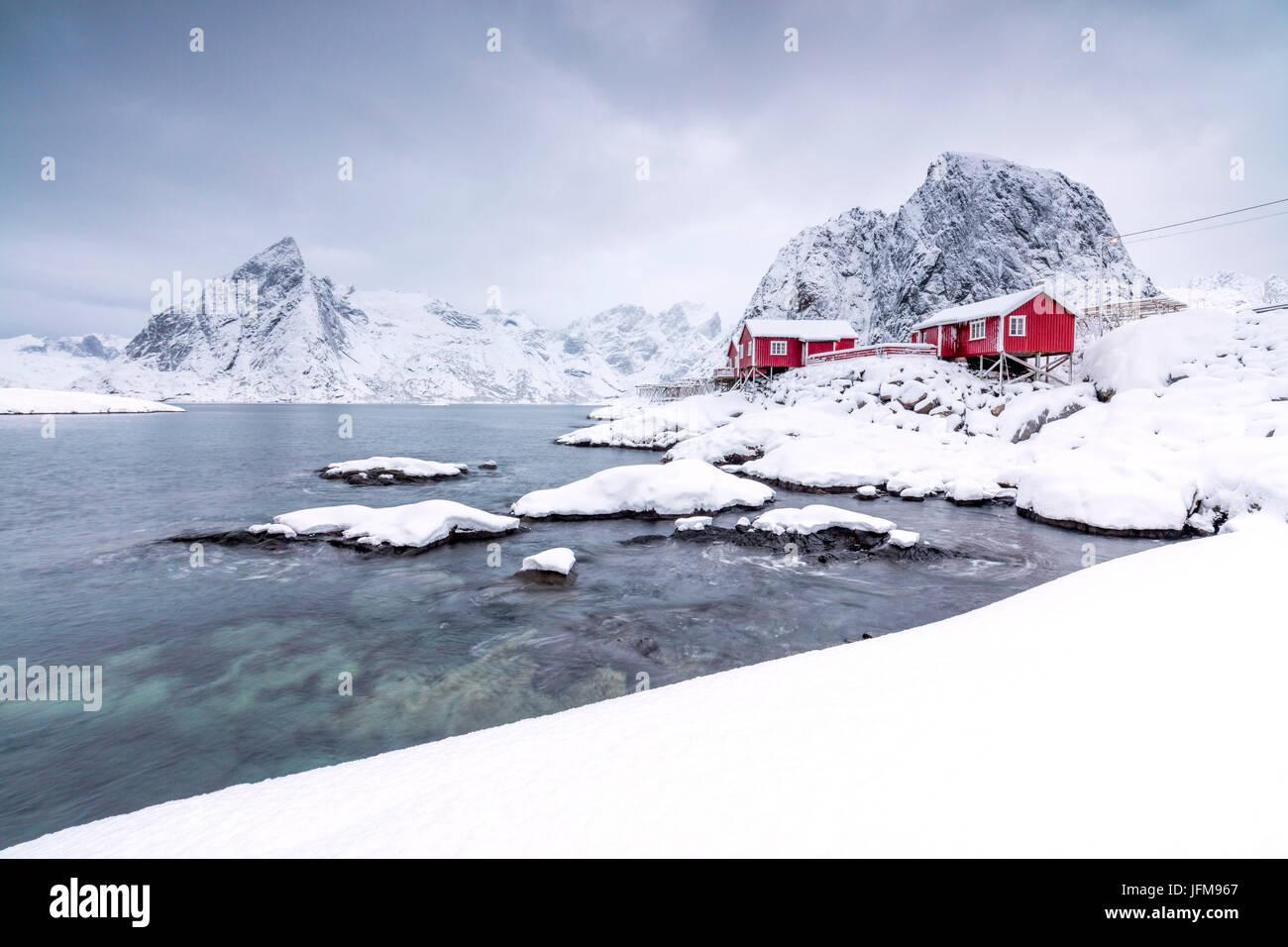 Die schneebedeckten Gipfel und gefrorene Meer umrahmen die typischen Fischer-Häuser genannt Rorbu Hamnøy Stockbild