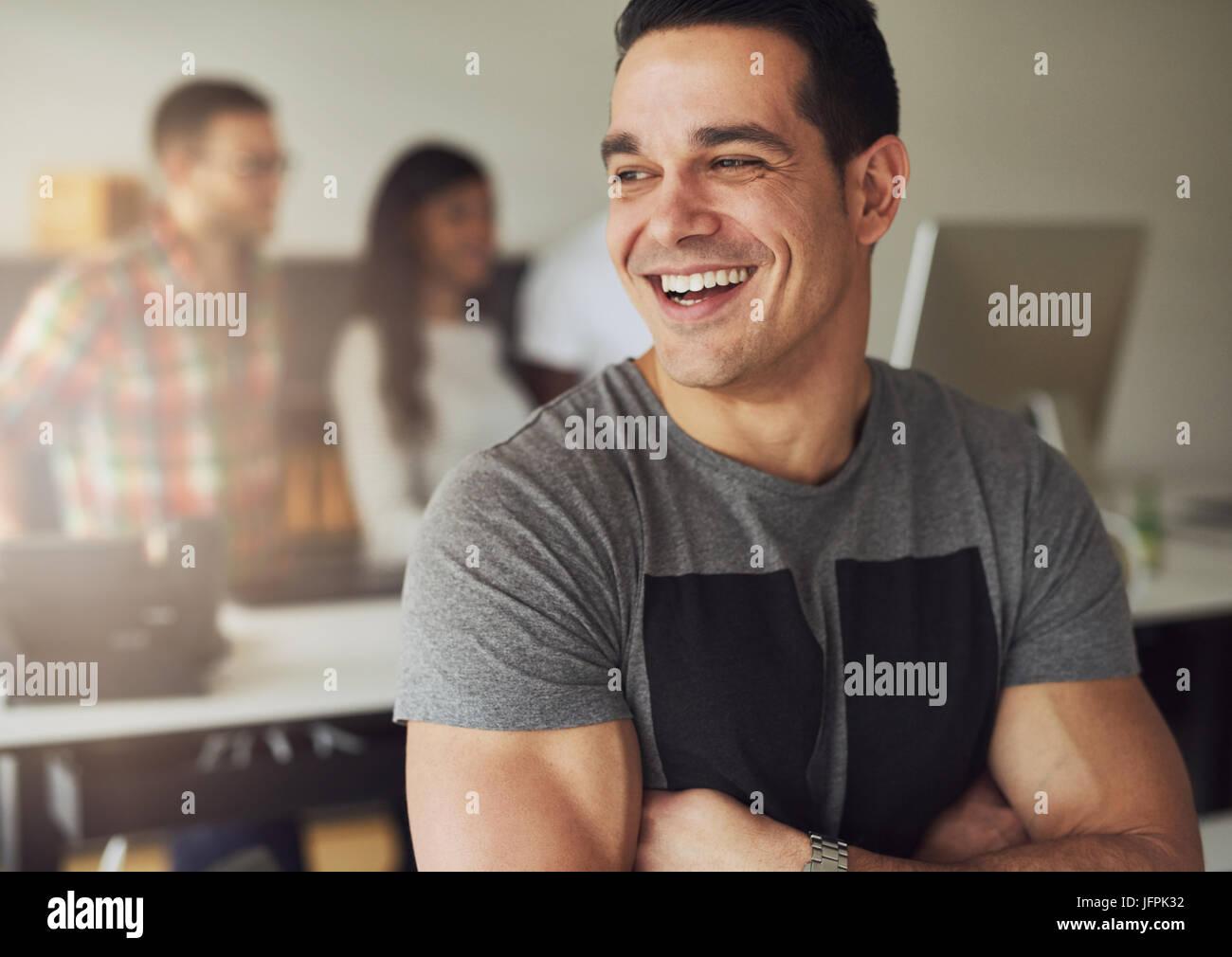 Lächelt zuversichtlich Jüngling mit Armen überquert stehend und wegschauen im Büro. Stockbild