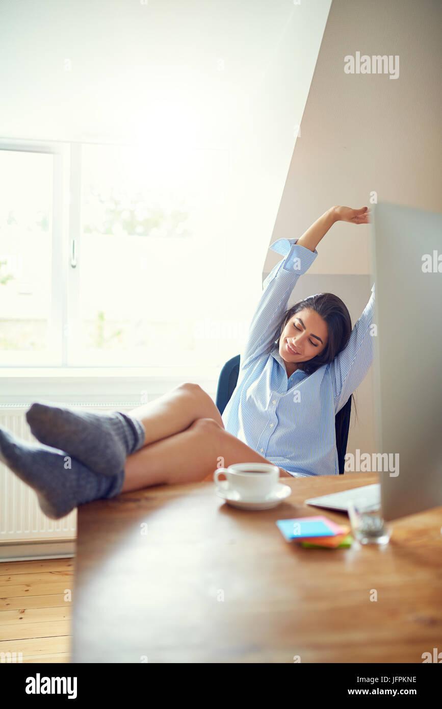 Dehnen junge Frau mit müden Ausdruck und Füße am Schreibtisch im home-Office. Kaffeetasse und Computer Stockbild