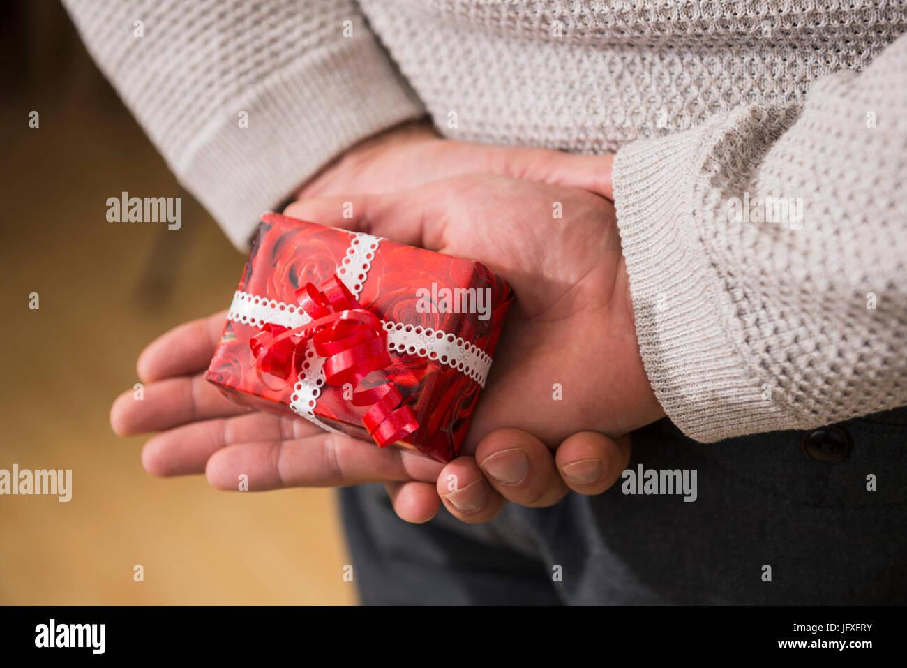 Mann hält Weihnachtsgeschenk hinter Rücken Stockfoto, Bild ...