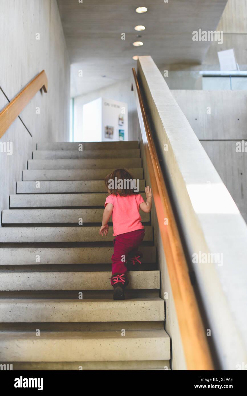 Ein kleines Mädchen klettert die Treppe in eine Kunstgalerie. Stockbild