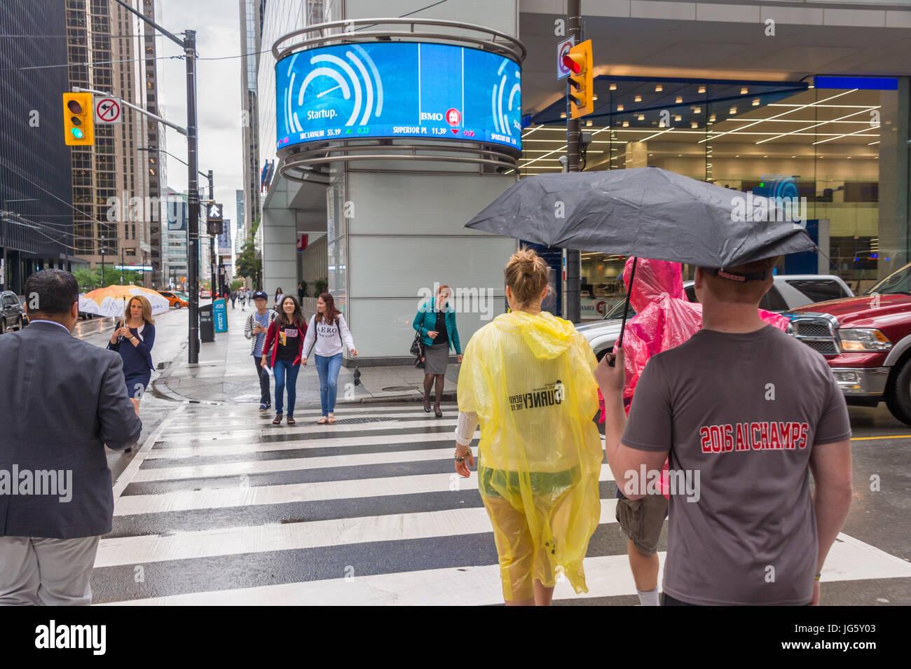 Toronto, Kanada - 26. Juni 2017: Menschenmenge mit Sonnenschirmen und Regenponchos an einem regnerischen Tag Stockbild