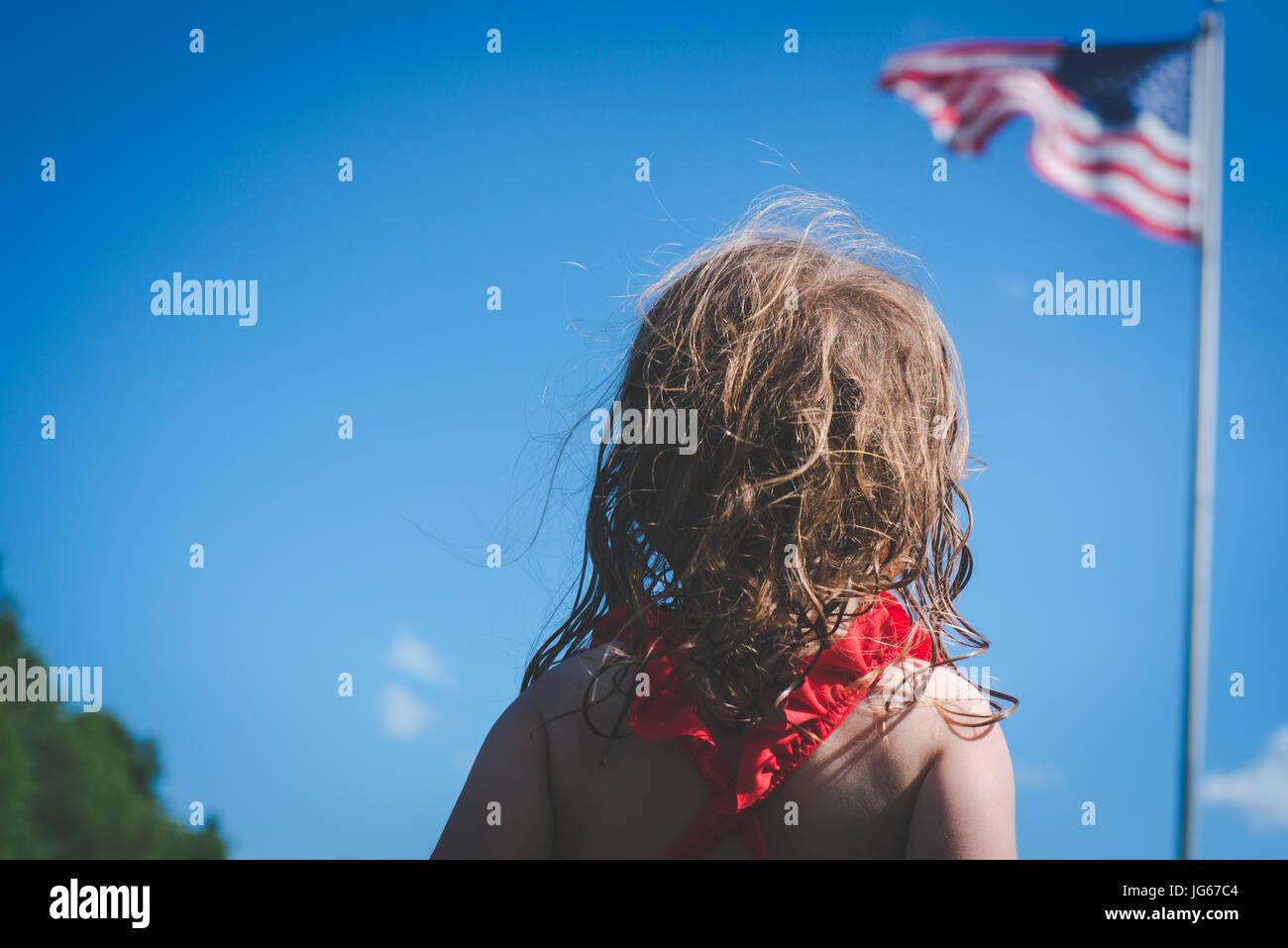 Ein junges Mädchen sucht an der amerikanischen Flagge. Stockbild