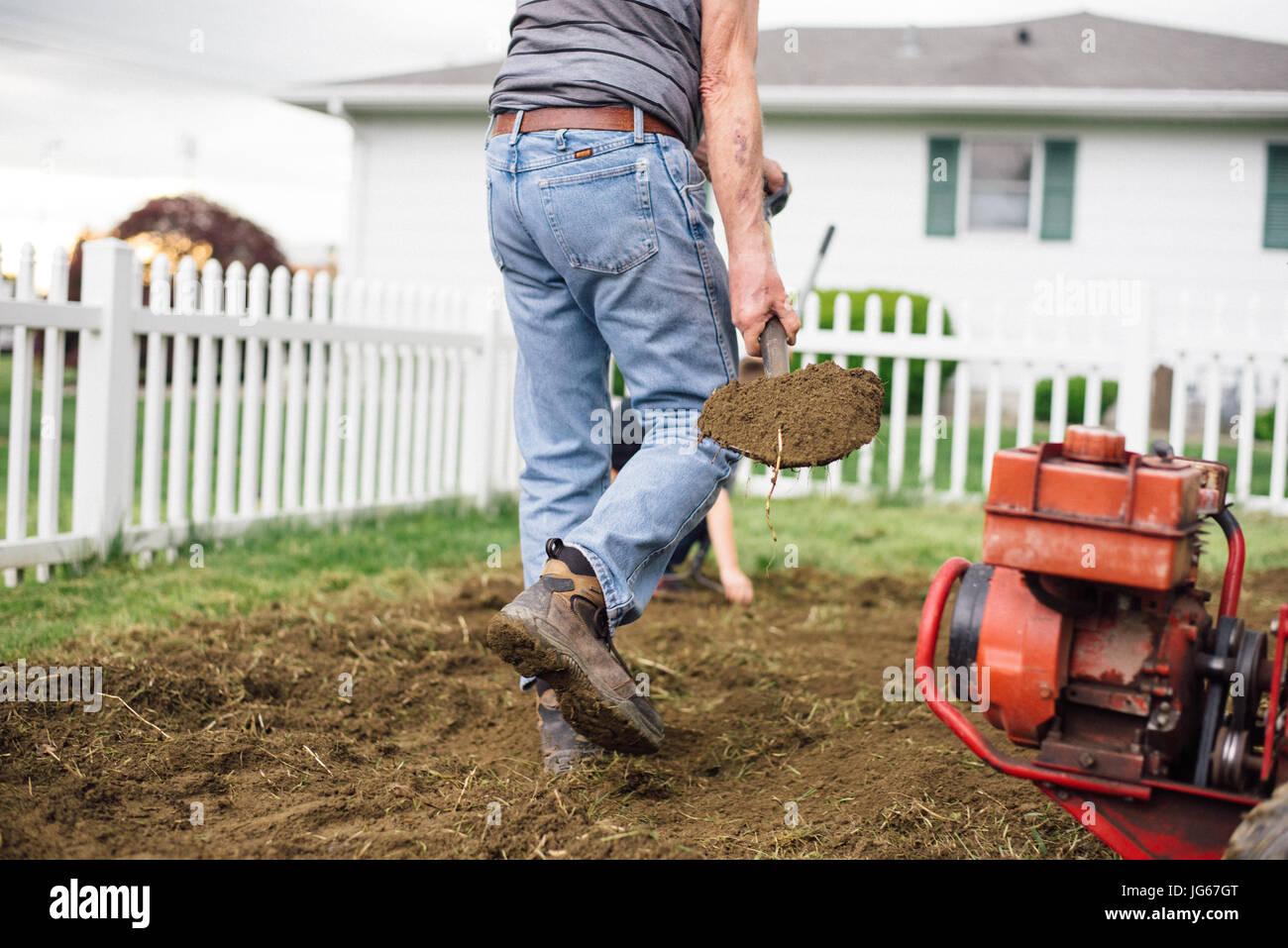 Ein Mann schaufeln Dreck in einem Garten neben einem rotatiller. Stockbild