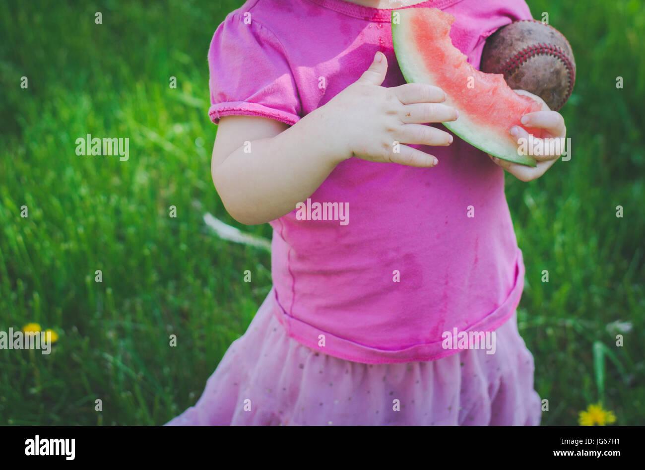Ein junges Mädchen isst eine Wassermelone und hält einen Baseball im Sommer Stockbild