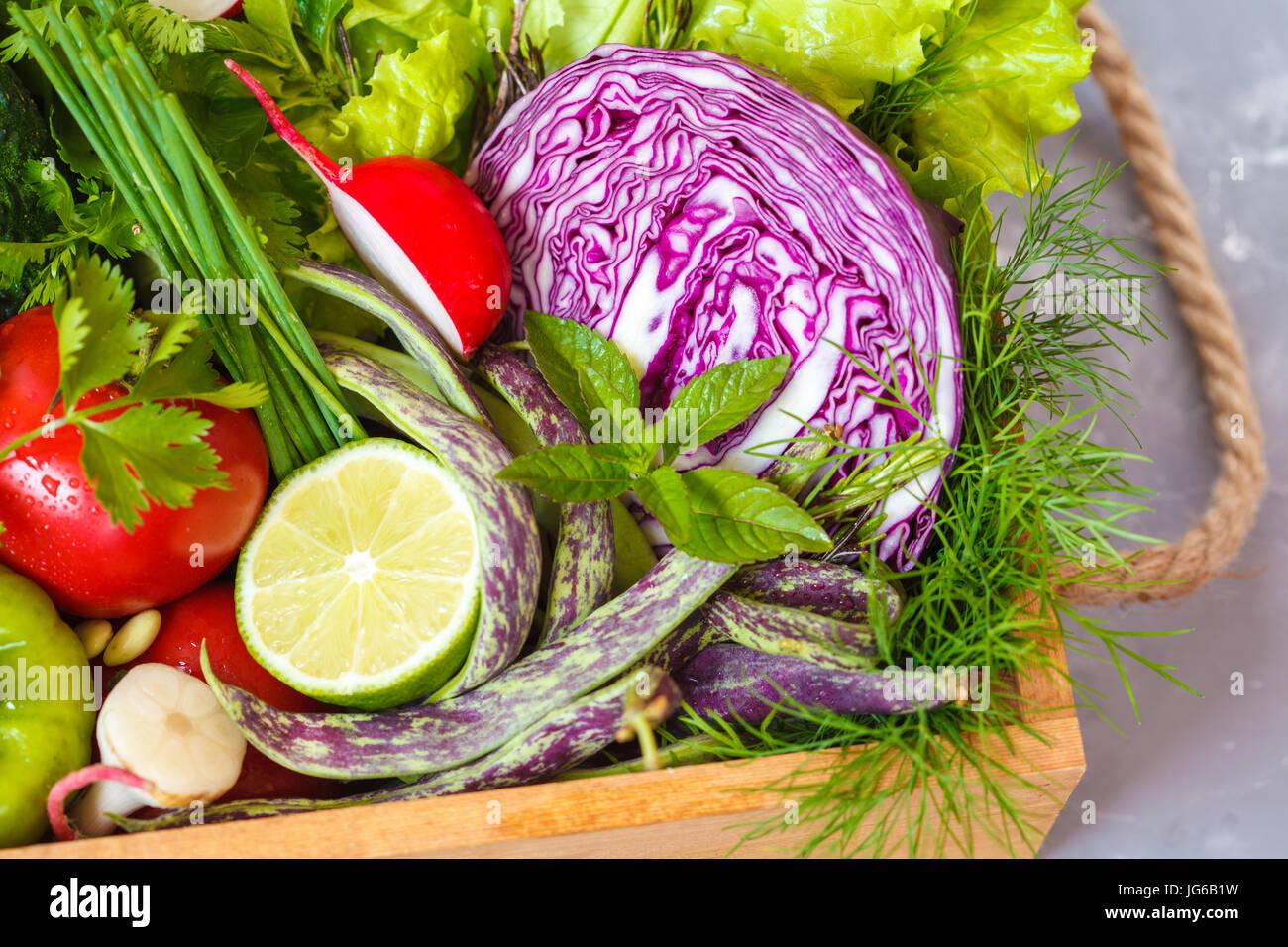 Sommergemüse in einer Holzkiste. Liebe für eine gesunde vegane Ernährung Konzept. Stockbild