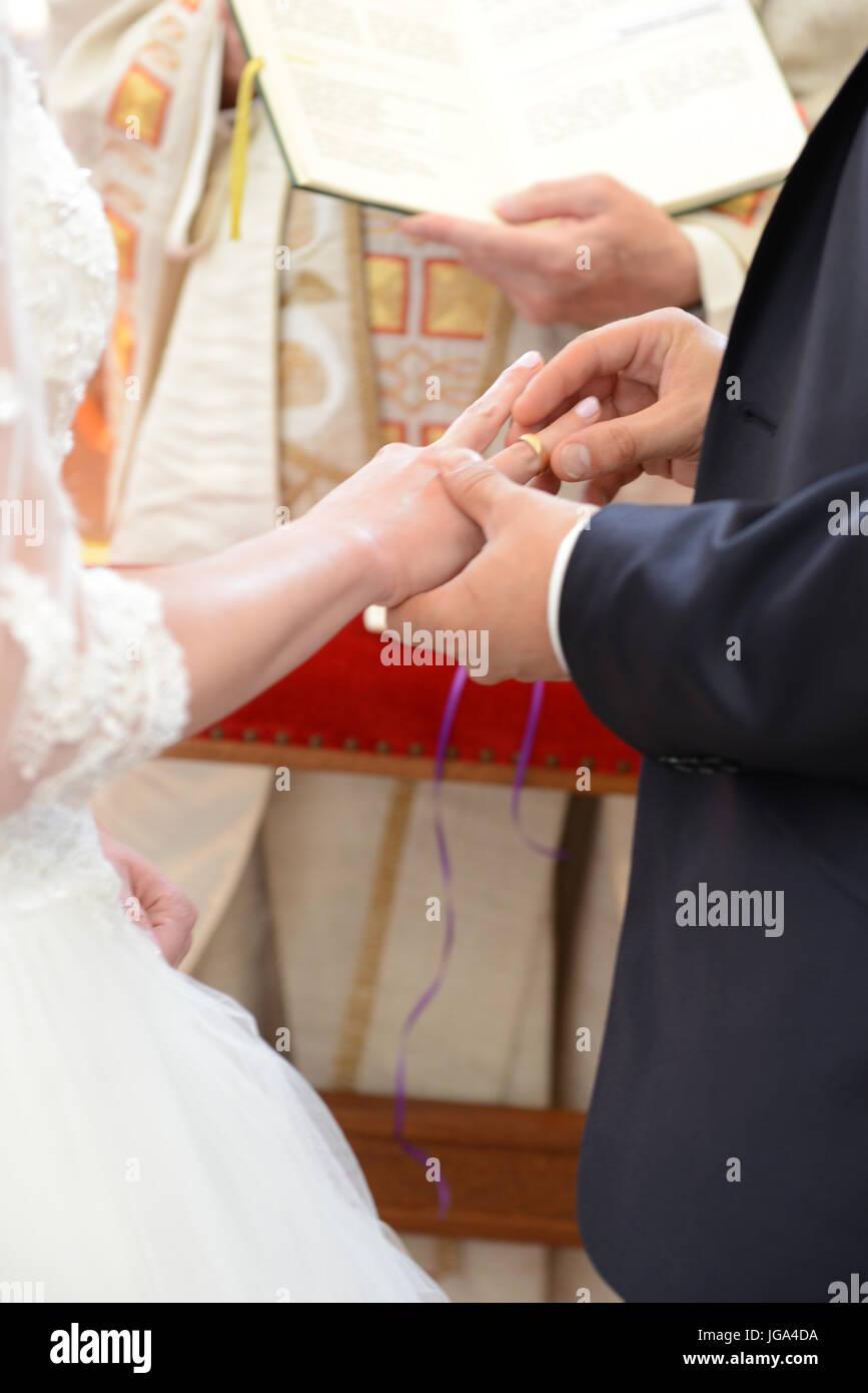 Braut ein Bräutigam tauschen ihre Eheringe in Kirche, Priester hielt Hochzeit Buch Stockbild