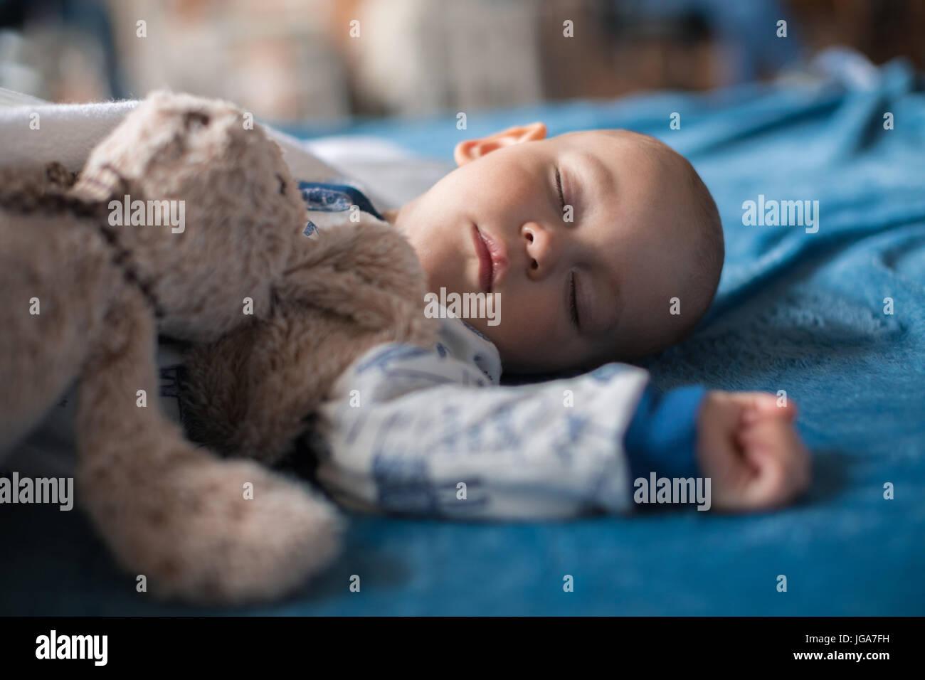 Niedliche Babyjungen schlafen mit Teddybär Stockbild
