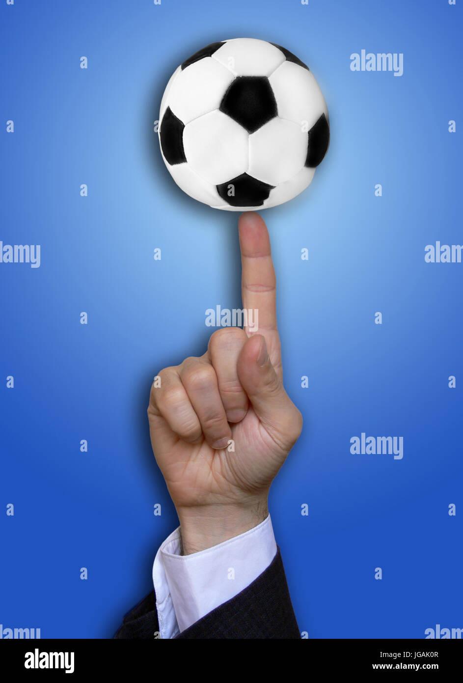 Hand des Menschen mit dem Finger halten einen kleinen Ball, Fußball-Business-Konzept Stockbild