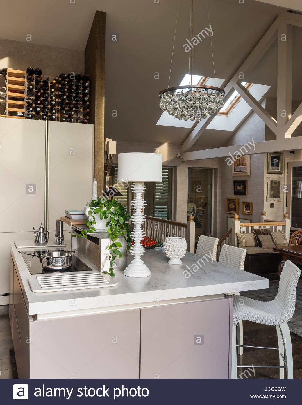 Glühbirne-Anhänger und Weinregal über Frühstücksbar in a-förmige Küche Stockbild