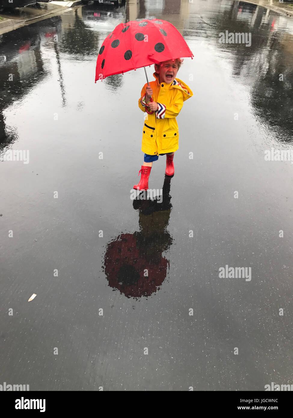 Weinende junge trägt einen Regenmantel und Wellington Stiefel stehen im Regen mit einem Regenschirm, Orange Stockbild