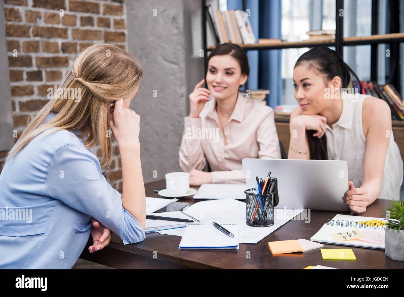 schönes Lächeln multikulturelle Geschäftsfrauen diskutieren Projekt am Arbeitsplatz mit laptop Stockbild