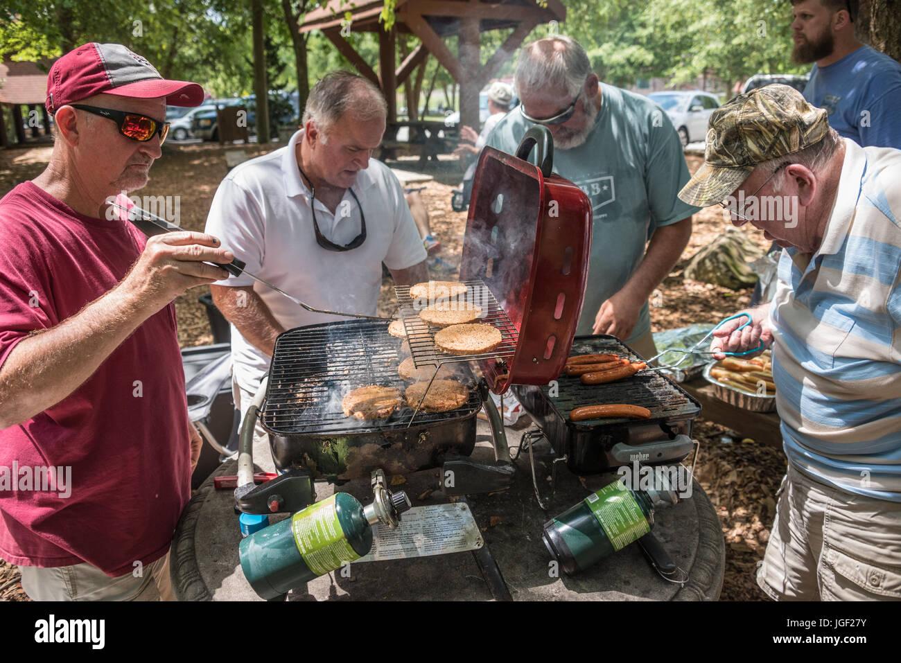 Männer Grillen Burger und Hot Dogs für einen Sommer-Familientag auf dem Chattahoochee River in Helen, Stockbild
