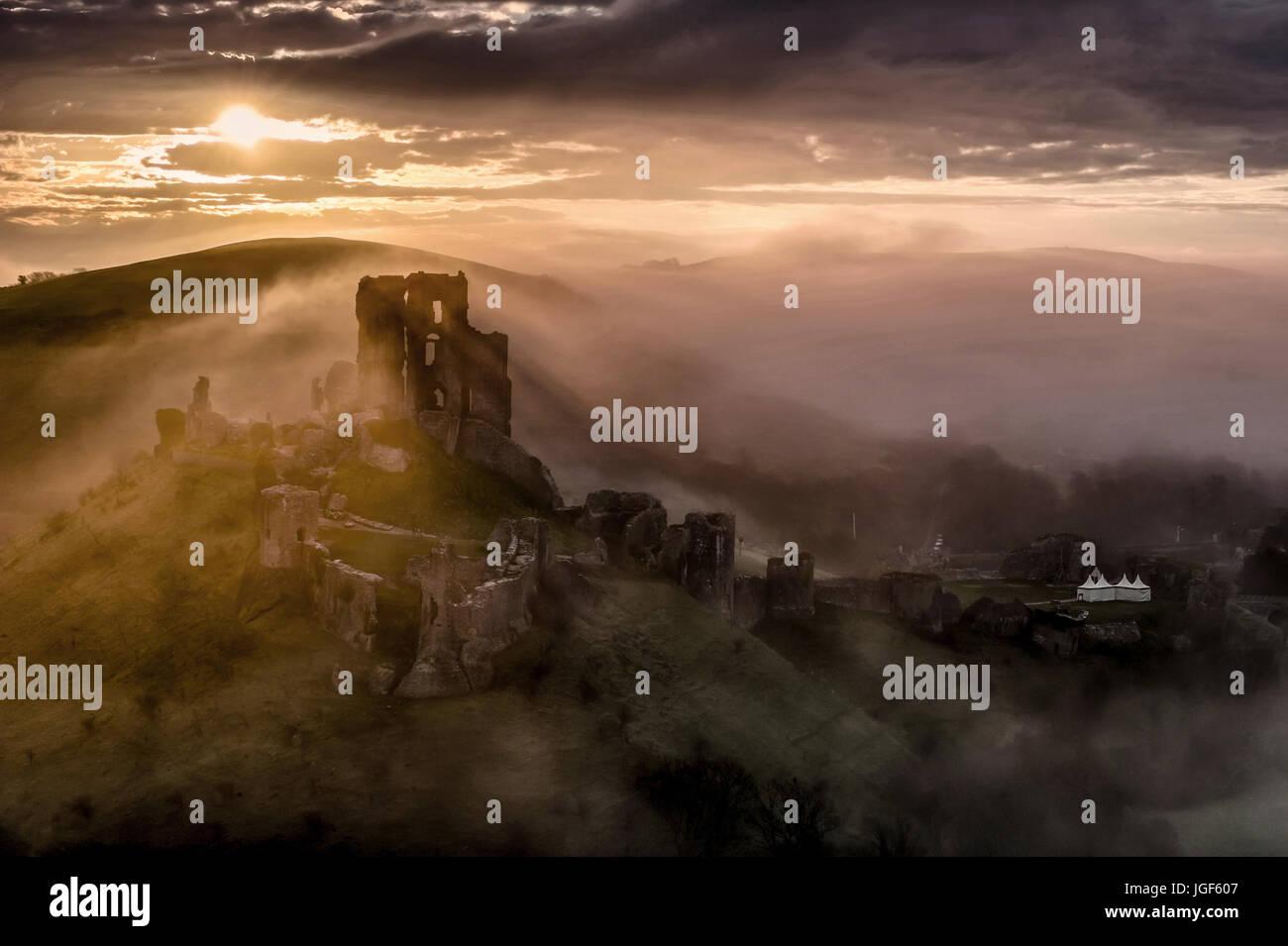 Corfe Castle auf nebligen Sonnenaufgang Stockbild