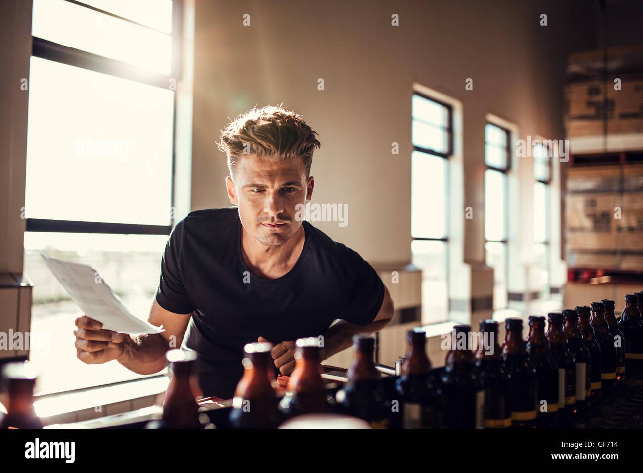 Brauerei Fabrikarbeiter untersucht die Qualität des Craft Beer. Junger Mann Inspektor arbeitet an Alkohol Herstellungsfabrik Stockbild