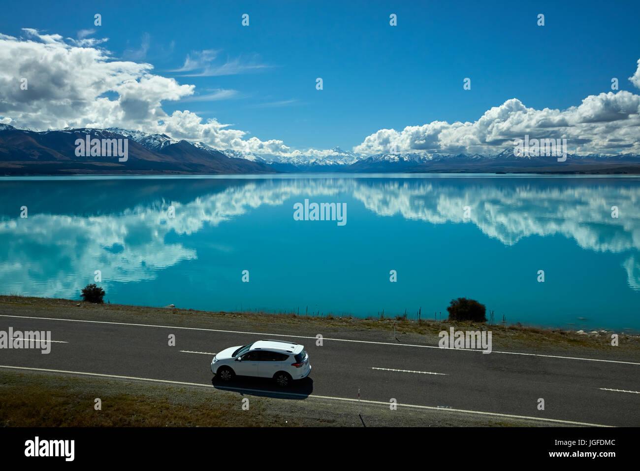 SUV auf den State Highway 8 und Aoraki / Mount Cook spiegelt sich in Lake Pukaki, Mackenzie Country, Canterbury, Stockfoto