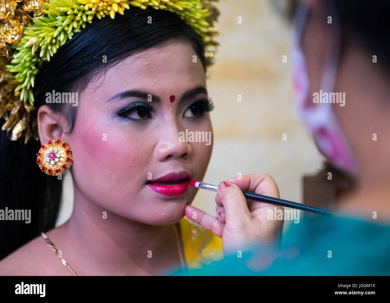 Eine Frau beim Schminken, ein junges Mädchen in Tracht vor einen Zahn Einreichung Zeremonie, Insel Bali, Canggu, Stockfoto