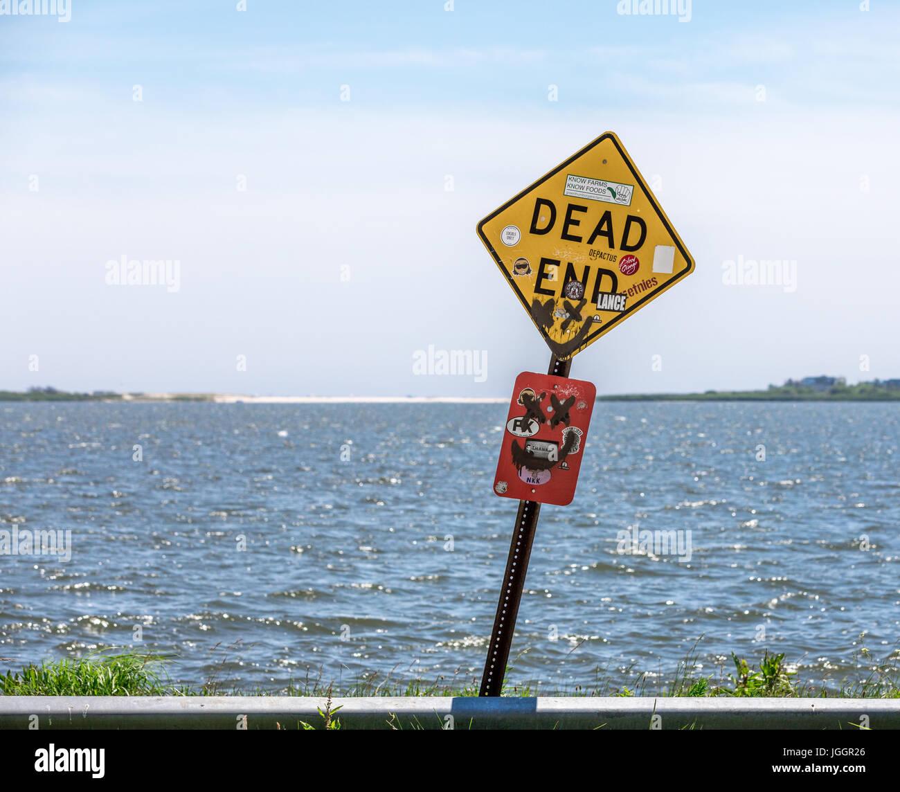 alte und misshandelte Dead-End-Zeichen am Ende einer Straße mit Wasser dahinter Stockbild