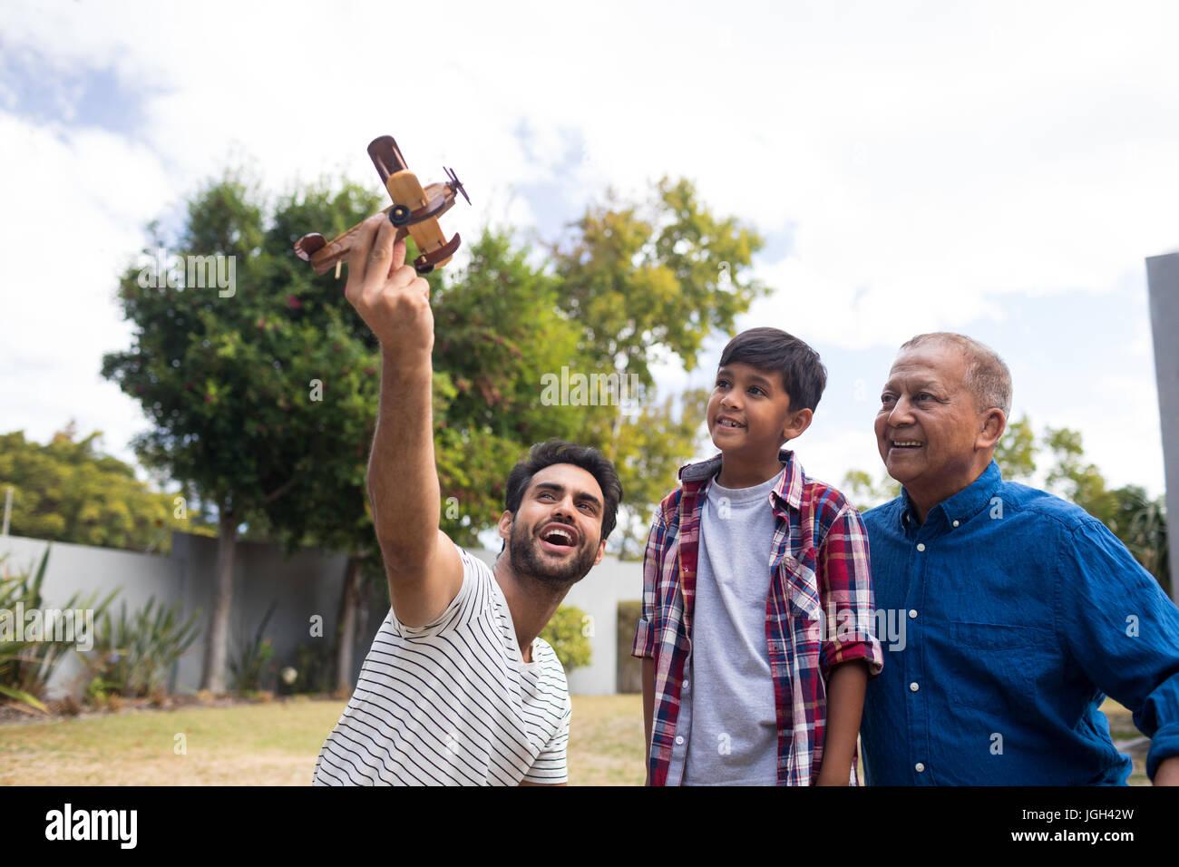 Junge mit Großvater Blick auf Menschen, die halten Spielzeugflugzeug beim Spielen im Hof Stockbild
