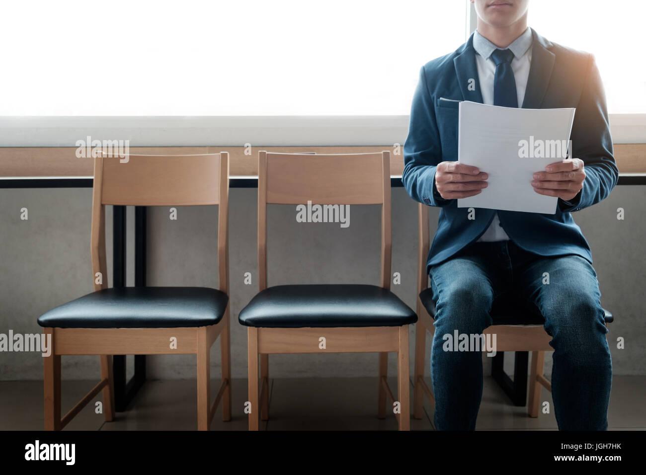 Zuversichtlich junger Geschäftsmann Papier halten, während Sie auf eine Reihe von Stühlen, sitzen Stockbild